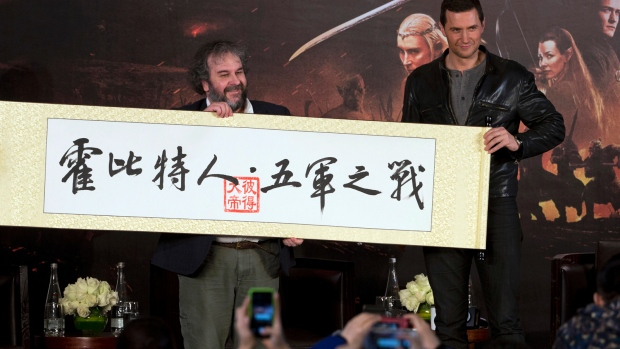 Director Peter Jackson, left, and actor Richard Armitage pose for photos while holding a Chinese calligraphy with the words: 'The Hobbit, The Battle of the Five Armies' during a press conference in Beijing, Monday, Jan. 19, 2015. (AP / Ng Han Guan)